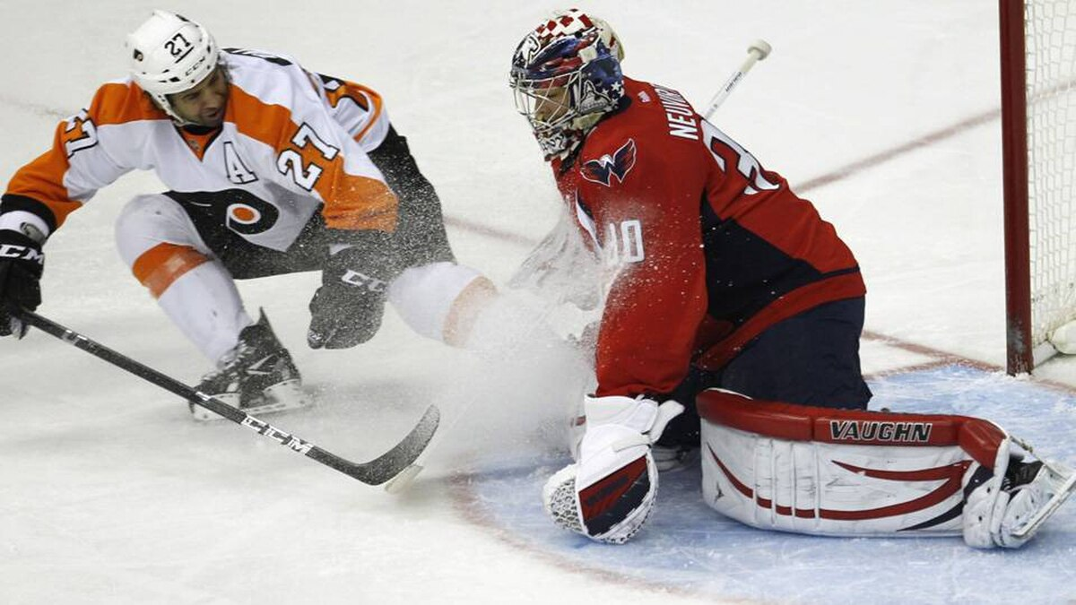 Washington Capitals' goalie Michael Neuvirth stops Philadelphia Flyers' Maxime Talbot during their NHL hockey game in Washington.