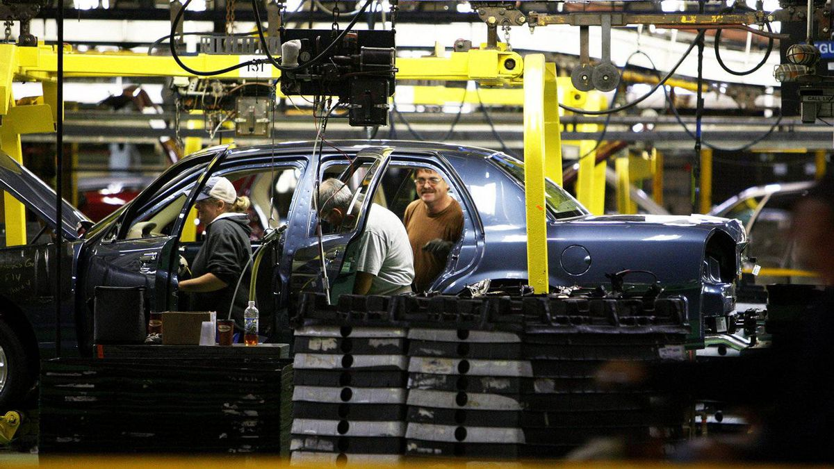 Ford employees work on the interior of a Crown Victoria.