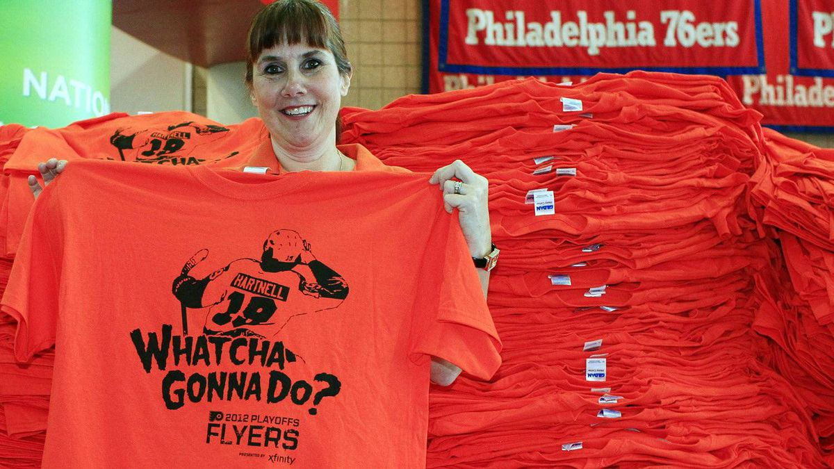 Dina Fisher, an employee at the Wells Fargo Center displays one of the thousands of orange T-shirts that Philadelphia Flyers fans will get before Game 3 in a first-round NHL Stanley Cup playoffs hockey series against the Pittsburgh Penguins, Sunday, April 15, 2012, in Philadelphia. The image is of Scott Hartnell above the phrase made famous by professional wrestler Hulk Hogan. (AP Photo/Tom Mihalek)