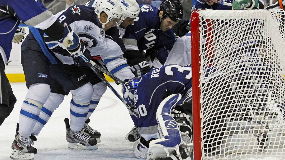 Tampa Bay Lightning goalie Dwayne Roloson (30) makes a save in front of Winnipeg Jets' Evander Kane (9) and Dustin Byfuglien as they are defended by Eric Brewer (2) during the third period of their NHL hockey game in Tampa, Florida October 29, 2011. The Bolts won 1-0. REUTERS/Mike Carlson