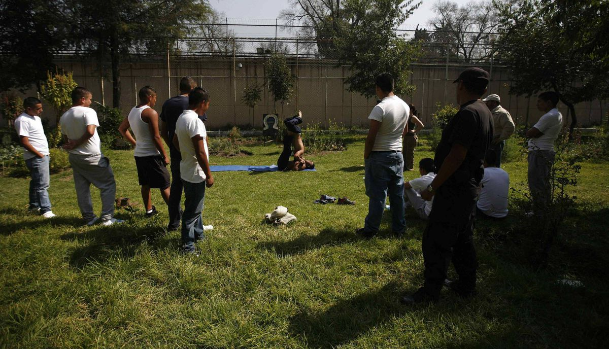 Inmates look at a demonstration during a yoga class inside a juvenile detention centre in Mexico City November 16, 2011.