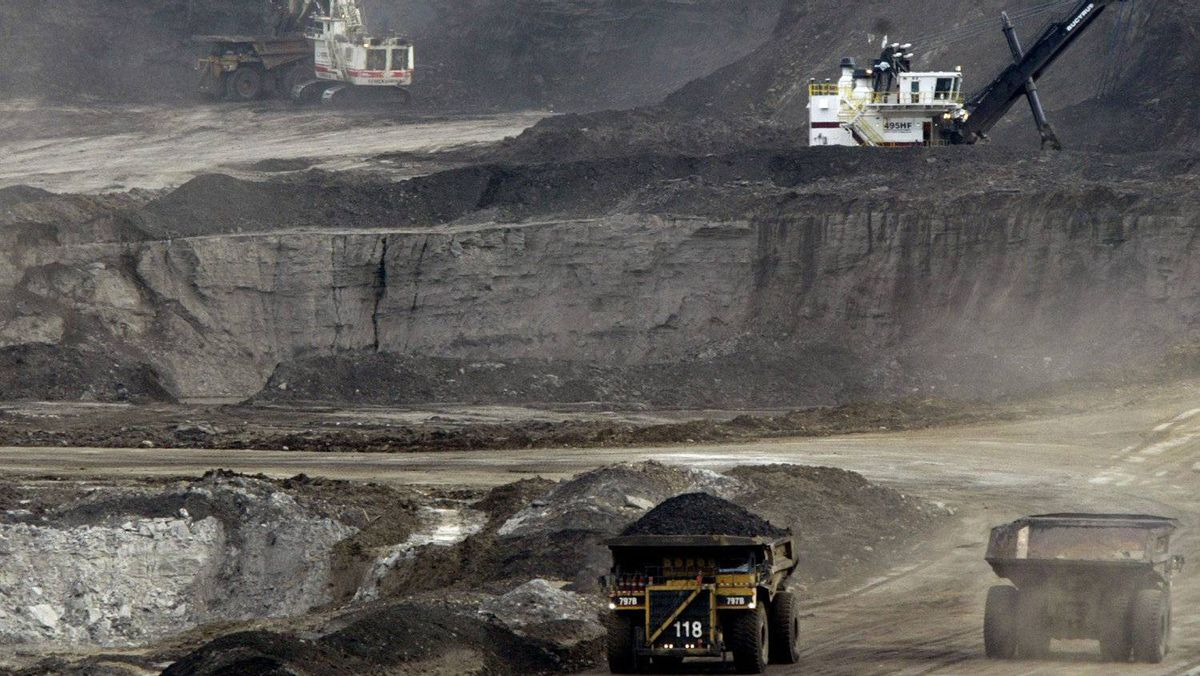 Mining trucks carry loads of oil-laden sand at the Albian Sands oil sands project in Fort McMurray, Alta.