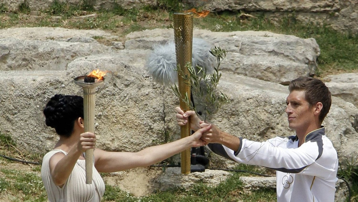 Greek actress Ino Menegaki, playing the role of High Priestess, hands Spyridon Gianniotis (R), Greece's world champion of swimming, an olive branch during the torch lighting ceremony in ancient Olympia.