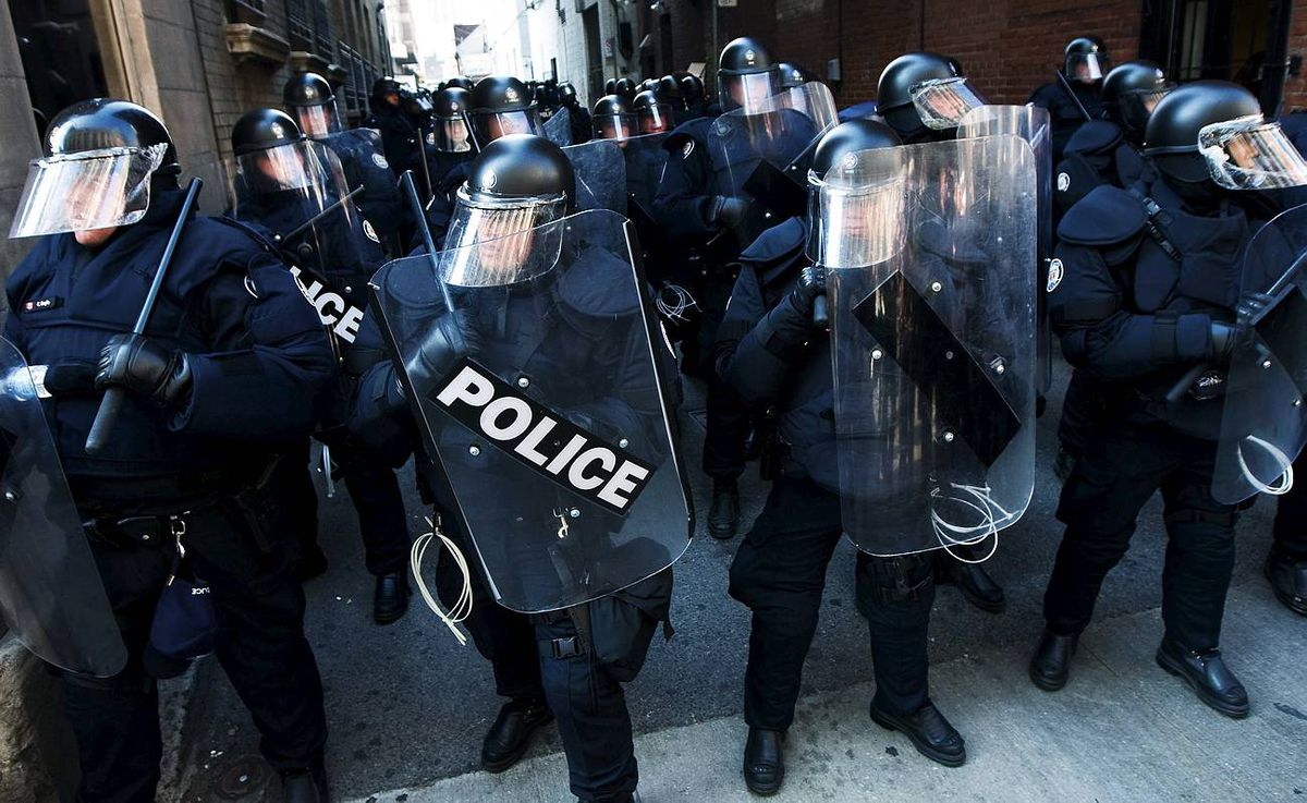 Riots police get ready to deploy as activists and protesters march along the streets of downtown Toronto.