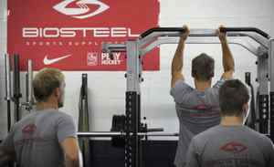 Players watch one of their own doing pullups.