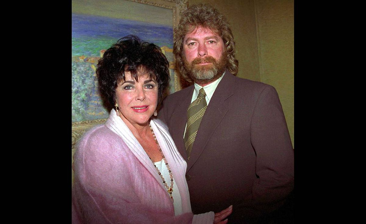 """Elizabeth Taylor poses with then husband Larry Fortensky as she launches her new fragrance """"Black Pearls"""" at Sotheby's in New York, Wednesday, June 14, 1995."""