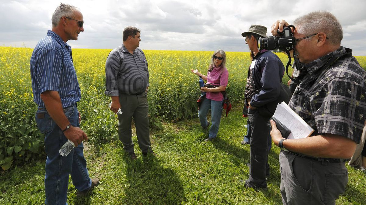 A group from Quebec talks to farmer Peter Sprunger about water issues while touring oil and gas operations near Rosemary, Alta.