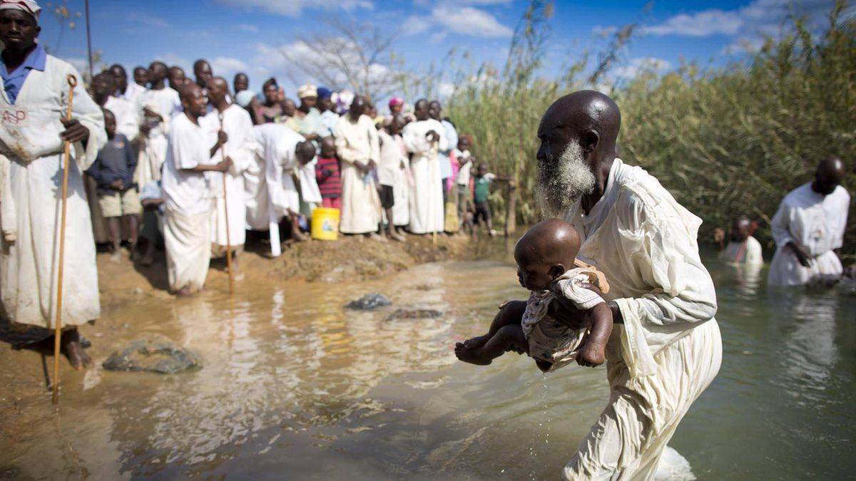A priest baptizes a child in a river outside Lubumbashi.