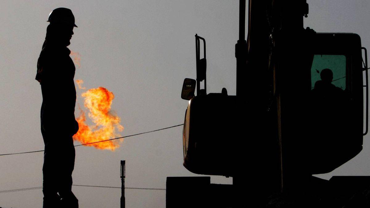 A gas flame burns behind oil field workers in Sakhir, Bahrain.