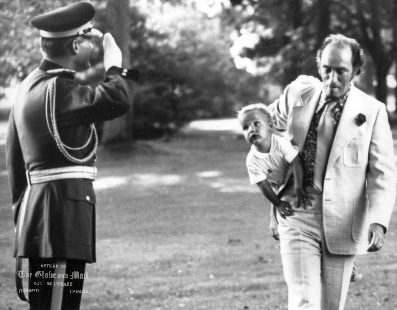 The notes transcribed from the back of this photograph are as follows: Prime Minister Pierre Trudeau walks towards the camera, cradling a young Justin under his arm like a football, while at left a uniformed RCMP officer performs a smart salute at Government House in Ottawa, August 10, 1973. Photo by Peter Bregg / CP