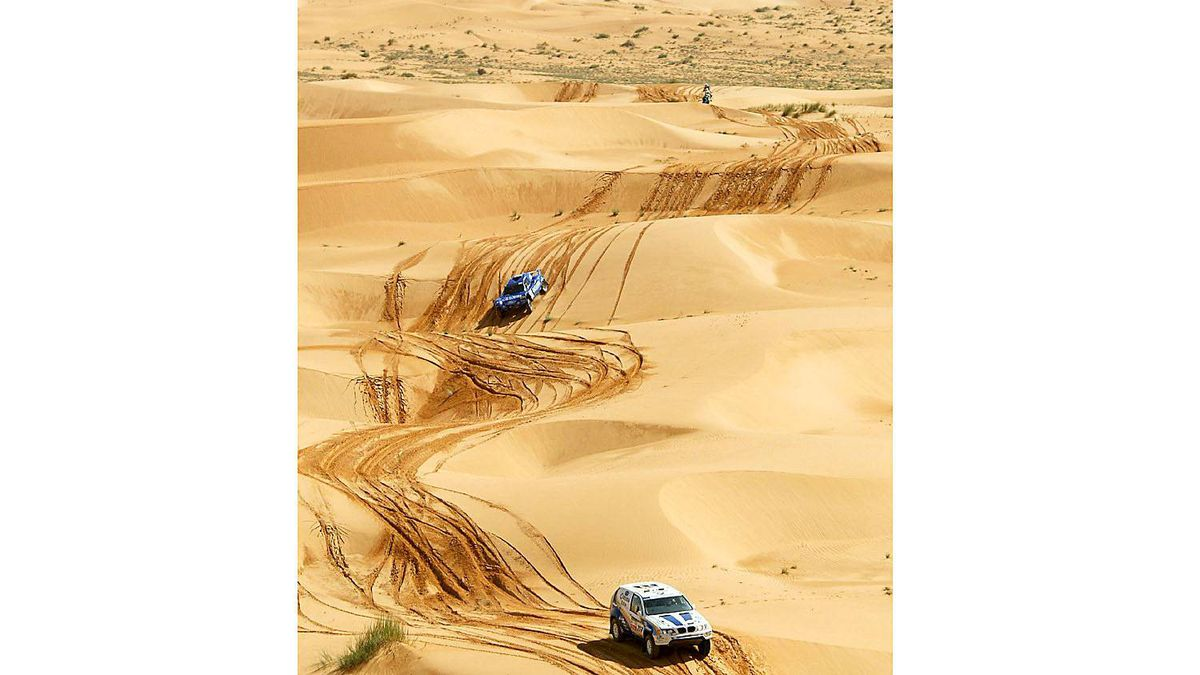 French driver Luc Alphand steers his BMW X4 followed by compatriot Jean-Louis Schlesser during the 15th stage between Tidjika and Nouakchott in Mauritania, for the 26th edition of the Dakar rally.