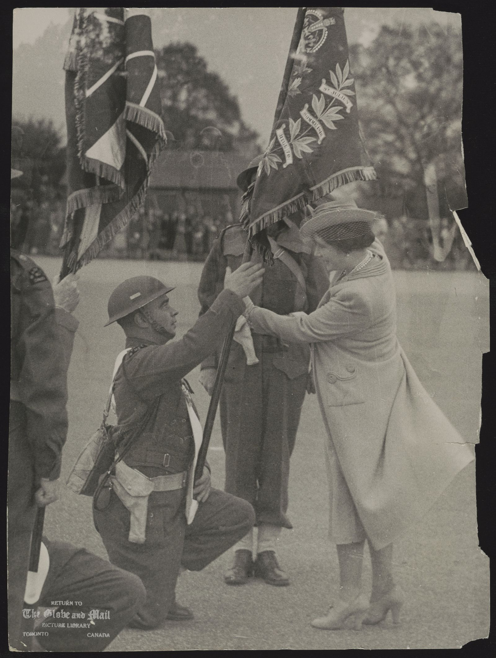 ROYAL FAMILY GREAT BRITAIN QUEEN ELIZABETH, QUEEN MOTHER PASSED BY THE CENSOR - NO. 168971 THE QUEEN PRESENTS COLOURS TO THE SASKATOON LIGHT INFANTRY, NOW IN ENGLAND. THE COLOURS WERE THE GIFT OF CITIZENS OF SASKATOON, CANADA. ASSOCIATED PRESS PHOTO SHOWS: THE QUEEN PRESENTS COLOURS. 25/10/41 [1941] PLEASE NOTE: THIS IS A ROTA PICTURE AND OTHER AGENCIES HAVE THE SAME PICTURE FOR CIRCULATION FL/AB 242101 251041S NY.AM.T.C9.C1