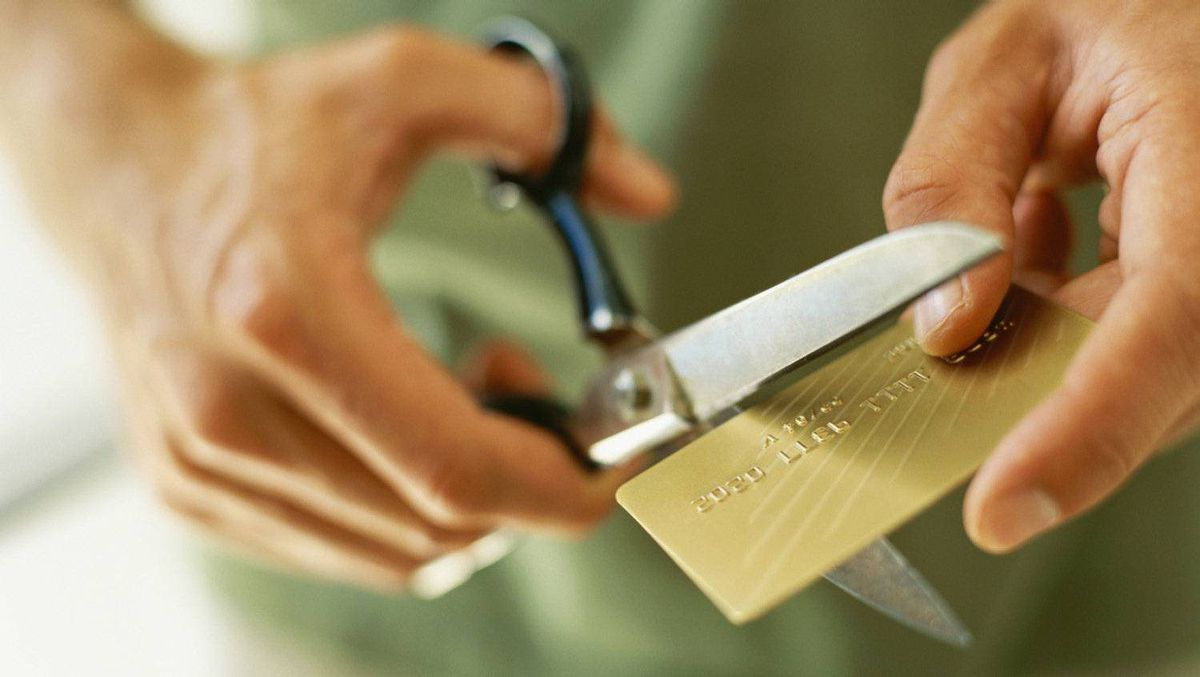 Hands cutting a credit card with scissors.
