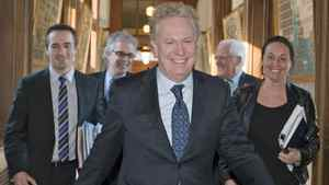 Flanked by his staff, Quebec Premier Jean Charest walks to Question Period at the National Assembly on Feb. 15, 2011.