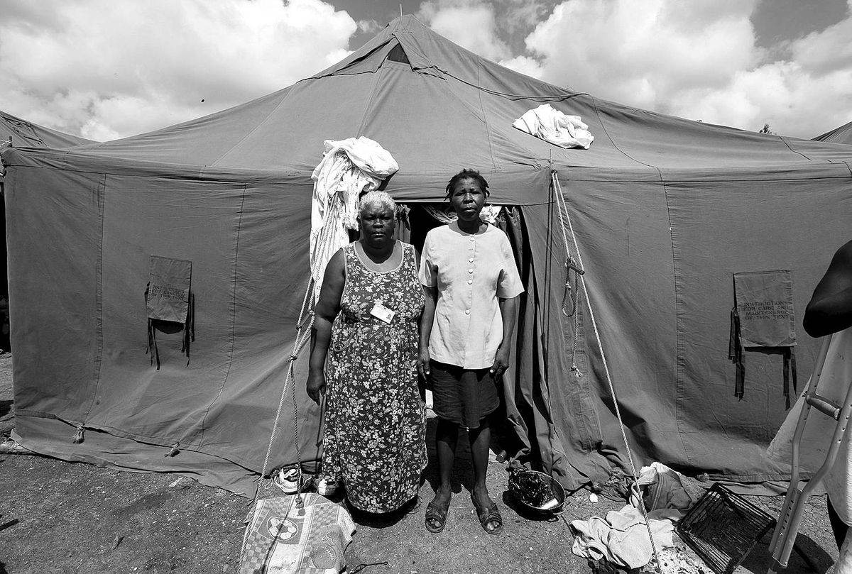 Feb. 12/09 - Jean McFins and her sister Jedus McFins stand in front of their tent in Pinchinat Soccer Feild Tent City for Internally Displaced Persons in Jacmel, Haiti, where they have been living in the 30 days since the earthquake that devastated Haiti.