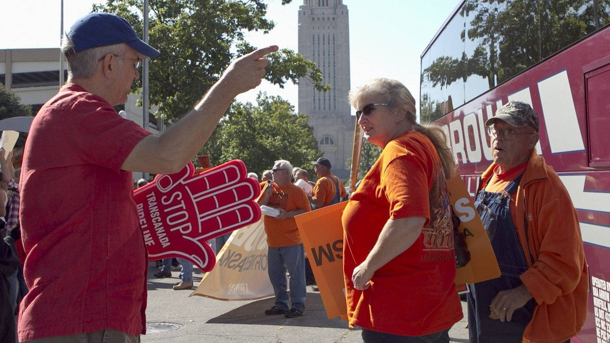 Demonstrators for the Keystone XL pipeline, right, and a demonstrator against the pipeline meet outside Pershing Auditorium near the state Capitol in Lincoln, Neb.
