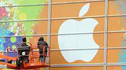 Workers apply the Apple logo to the exterior of the Yerba Buena Center for the Arts