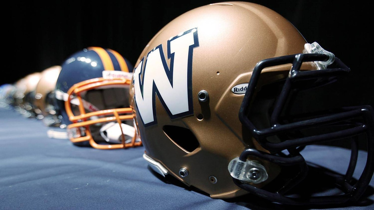 The new Winnipeg Blue Bombers 1980s-style logo is unveiled at a press conference at Canada Inn Stadium in Winnipeg, Tuesday, April 24, 2012. The CFL club is changing its helmet logo back to a simple 'W'. THE CANADIAN PRESS/John Woods