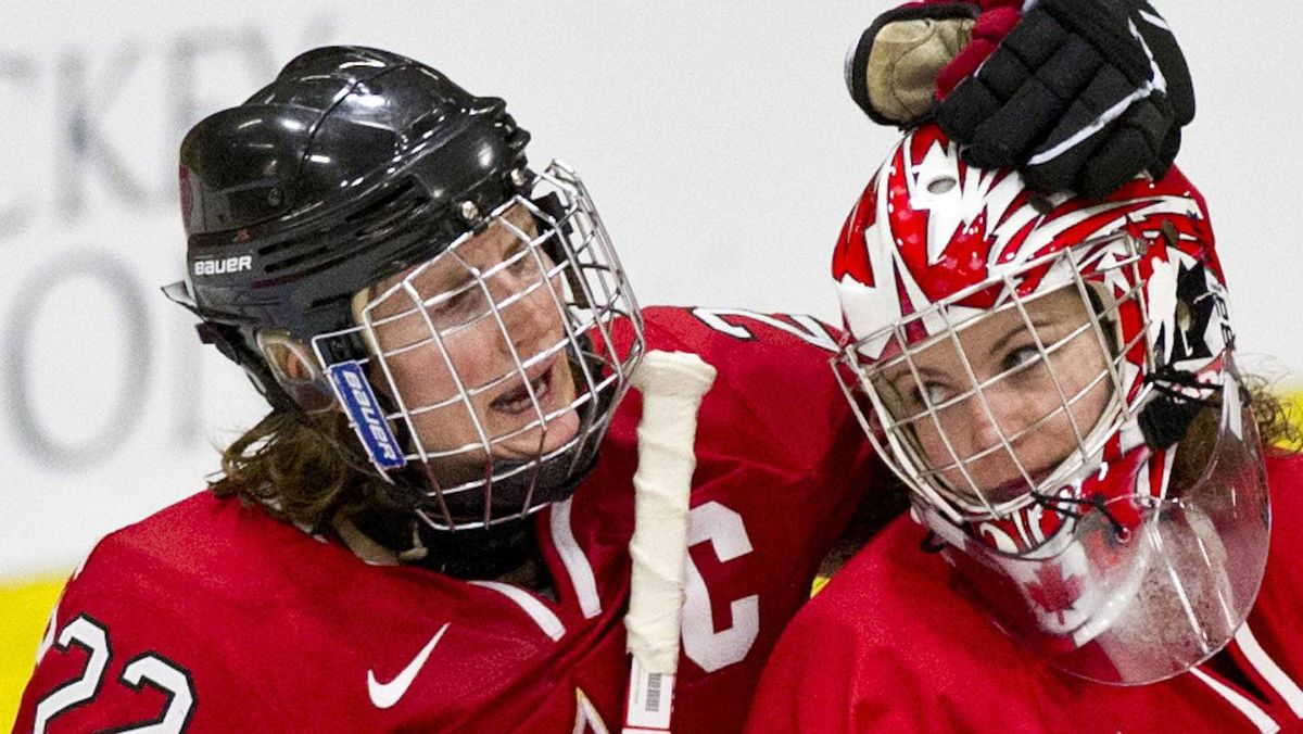 Team Canada Hayley Wickenheiser celebrates with goaltender Shannon Szabados their 5-1 victory over Team Finland in semi-final hockey action at the World Women's Ice Hockey Championships Friday, April 13, 2012 in Burlington, VT. Canada moves on to the final. THE CANADIAN PRESS/Paul Chiasson
