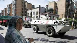 A Uighur woman stands near a small mosque where a paramilitary police Armored Personnel Carrier is parked in Urumqi, western China's Xinjiang province, Thursday, July 9, 2009.