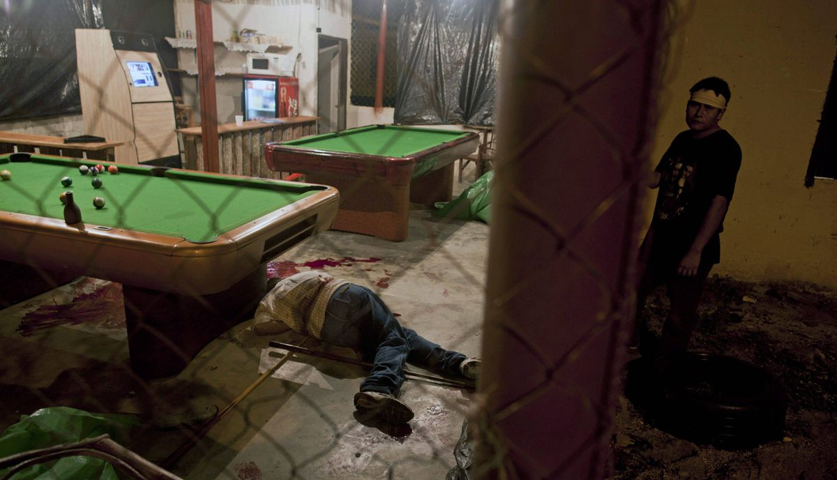 The body of Wilmer Orbera lies inside a pool hall after an attack by masked assailants in Choloma on the outskirts of San Pedro Sula, Honduras, MArch 11, 2012. Hondurans say gangs have imposed an almost unchallenged reign of extortion, murder and drug trafficking on this city and others.