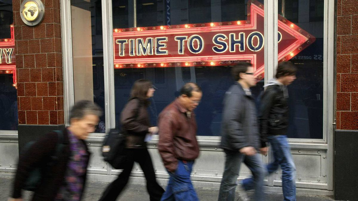 """People walk past a """"time to shop"""" sign in downtown San Francisco, California, in this December 9, 2008 file photo."""