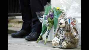 A police officer stands next to flowers and a teddy bear left outside the home of Amy Winehouse in London July 25, 2011.