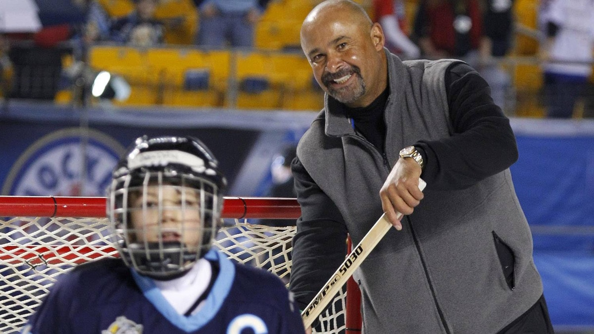 """Hockey Hall of Fame goalie Grant Fuhr, right, helps with an outdoor """"pond hockey"""" session with youth hockey players on a sheet of ice adjacent to the rink built for the NHL Winter Classic outdoor hockey game between the Pittsburgh Penguins and Washington Capitals in Heinz Field in Pittsburgh Saturday, Jan. 1, 2011. (AP Photo/Gene J. Puskar)"""