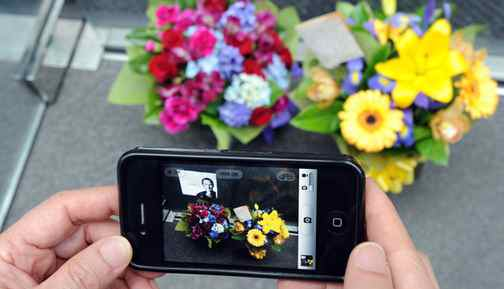 A passerby uses an iPhone 4 to photograph flowers left for the late Steve Jobs, co-founder of Apple, outside the Apple store in Sydney, Australia on October 6, 2011.
