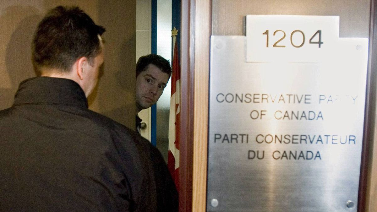 An unidentified staffer opens the door for a plainclothes RCMP officer during a raid on Conservative Party headquarters in Ottawa on April 15, 2008.