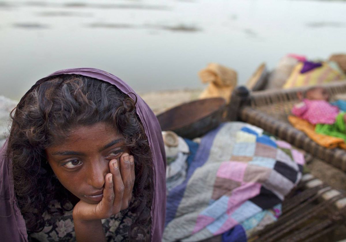 A flood victim sits on her bed along a road where many families are living after being forced to flee the flood waters August 24, 2010 in Shadadkot , Pakistan.