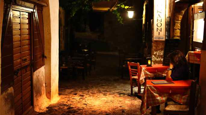 A woman sits outside her tavern in the medieval castle of Monemvasia May 29, 2012. Greece's sandy resorts, azure waters and ancient temples remain popular, but will not, it seems, be enough to pull it out of a fifth year of recession. The pain is already being felt - tourist receipts for the first quarter tumbled by 15.1 percent to 396.3 million euros from 466.7 million euros, the Bank of Greece said.