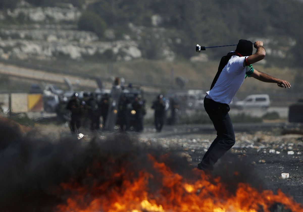 A Palestinian protester uses a sling to hurl stones at Israeli troops during clashes outside Ofer prison near the West Bank city of Ramallah May 15, 2012.