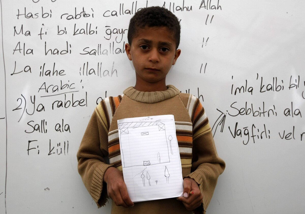 Udey Heyro, 10, a Syrian refugee, shows a drawing of his dream home during a class at a school for refugee children at Boynuyogun refugee camp in Hatay province near the Turkish-Syrian border.