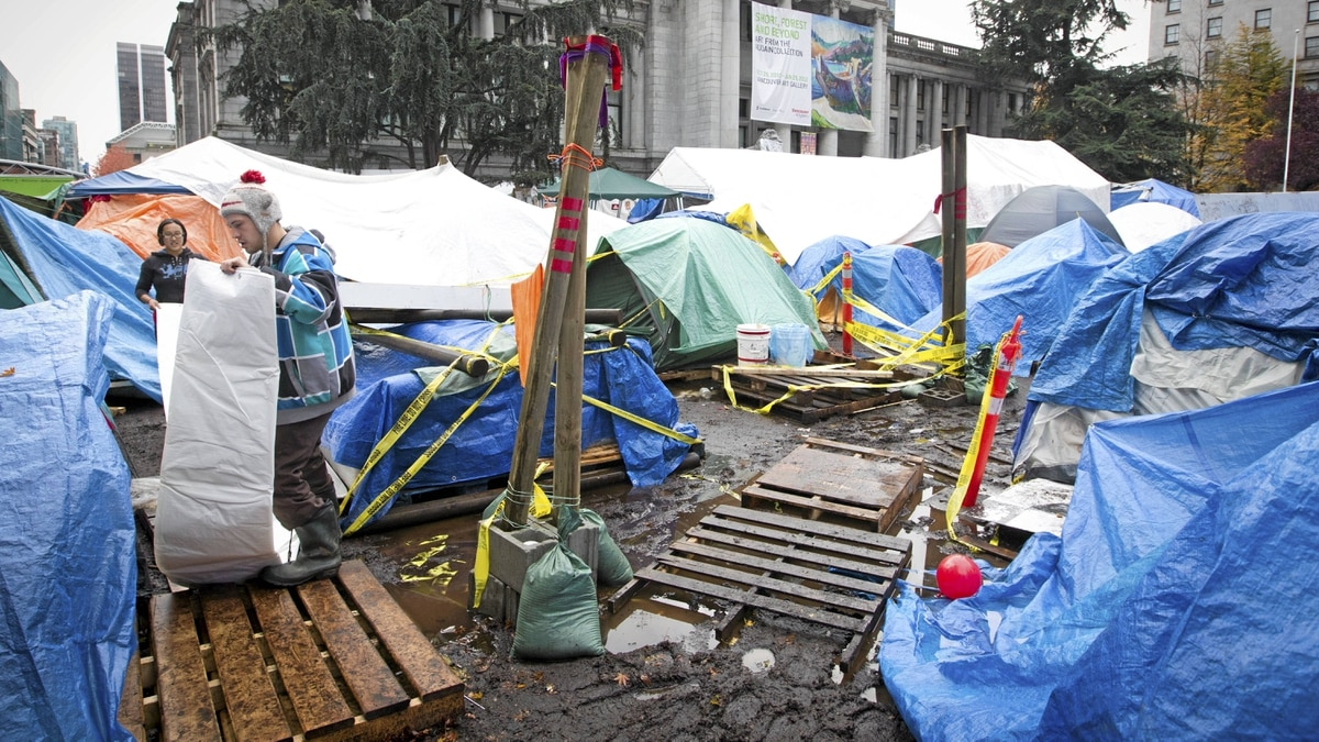 Two members of Occupy Vancouver hang a tarp over their tent as they prepare to dig in at the Vancouver Art Gallery, Nov. 8, 2011.