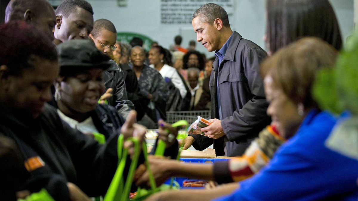 U.S. President Barack Obama pitches in a Washington foodbank on Nov. 23, 2011.
