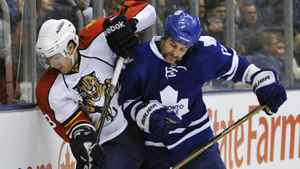 Toronto Maple Leafs forward Mike Brown, right, hits Florida Panthers forward Mike Santorelli into the boards during the first period of their NHL hockey game in Toronto February 1, 2011.