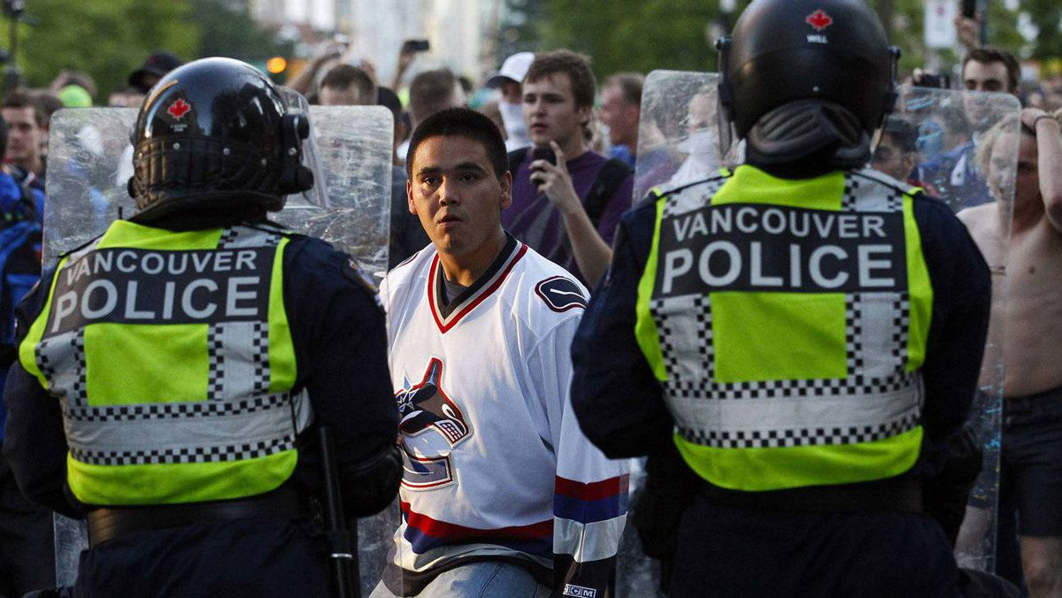 A Vancouver Canucks fan confronts the police during riots after the Canucks lost Game 7 of the NHL Stanley Cup final hockey game in Vancouver, British Columbia June 15, 2011.