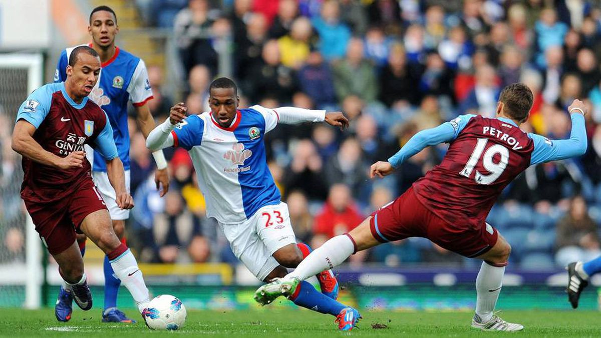 Blackburn Rovers' Junior Hoilett, center, is tackled by Aston Villa's Stiliyan Petrov, right, during the English Premier League soccer match at Ewood Park, Blackburn, England, Saturday March 3, 2012. The match ended in a 1-1 draw.