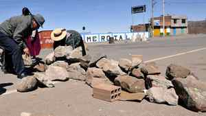 Locals block the road to the Desaguadero international bridge, linking Bolivia and Peru, during a protest against a mining project by a Canadian subsidiary, on May 16, 2011, in Desaguadero, 112 km west of La Paz. Both in Bolivia and in the Peruvian southeastern department of Puno, locals held the road blockade stating that the mining project will pollute the Desaguadero river and the Titicaca Lake.