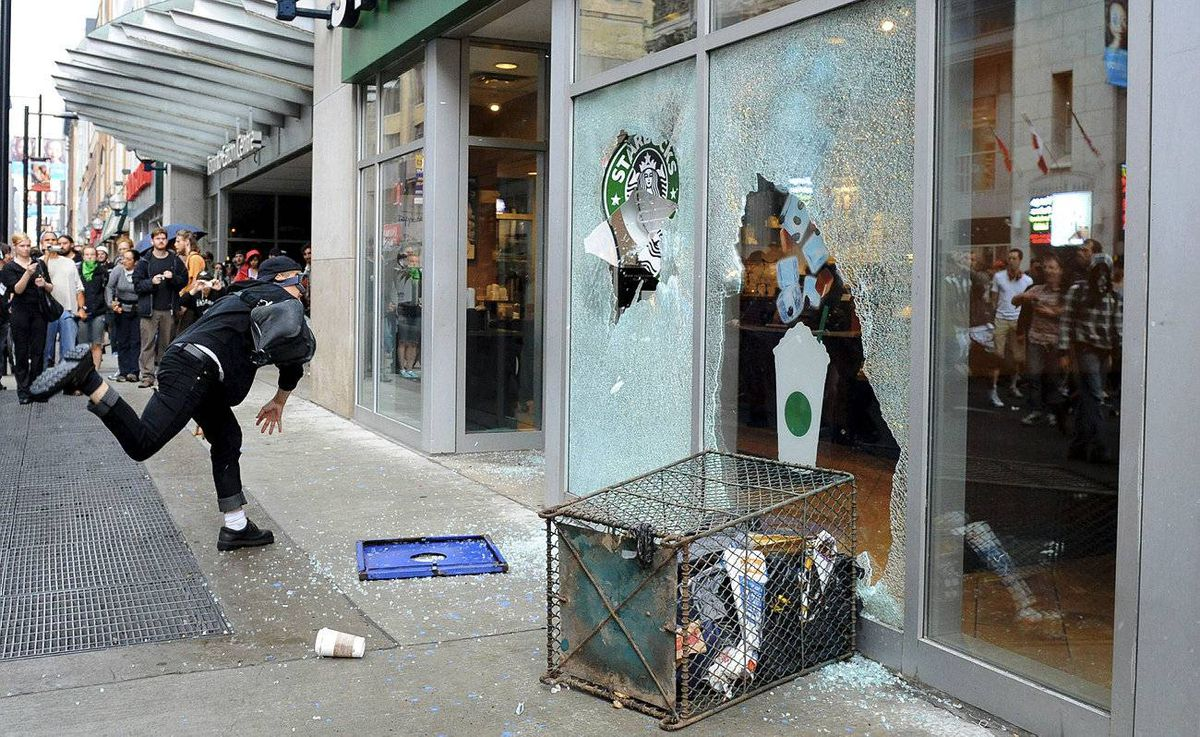 An G20 protester smashes a window at a downtown Toronto Starbucks.