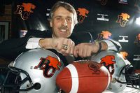 Former star B.C. Lions kicker Lui Passaglia shows off his Grey Cup rings during a news conference in Vancouver on Tuesday Dec. 18, 2001.