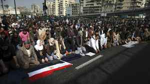 Locals pray in the street in front of The l-Istiqama Mosque watched by riot police in Giza on Jan. 28, 2011 in Cairo, Egypt.