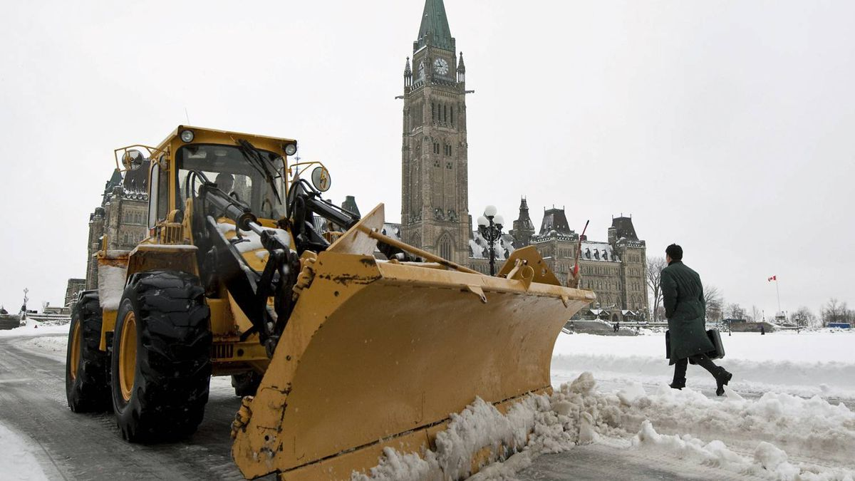 A snow plow clears slush around Parliament Hill amid heavy rain in Ottawa on March 10, 2011.