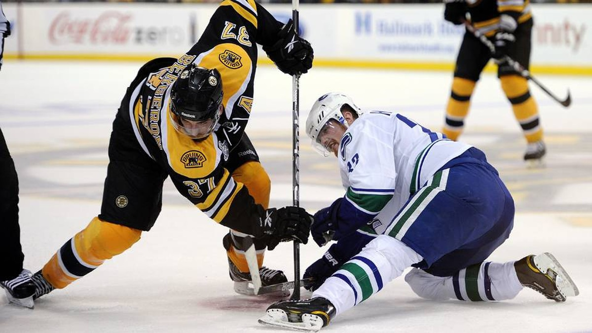 Patrice Bergeron of the Boston Bruins faces off against Henrik Sedin of the Vancouver Canucks.