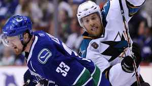 Joe Pavelski of the San Jose Sharks and Henrik Sedin of the Vancouver Canucks collide at centre ice. (Photo by Harry How/Getty Images)