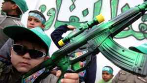 A Palestinian boy carries a toy gun spray painted green, the color of Hamas.