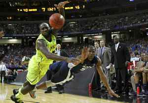 Baylor Bears forward Quincy Acy (L) and Xavier Musketeers guard Tu Holloway dive for the ball during the second half of their men's NCAA South Regional basketball game in Atlanta, Georgia, March 23, 2012.