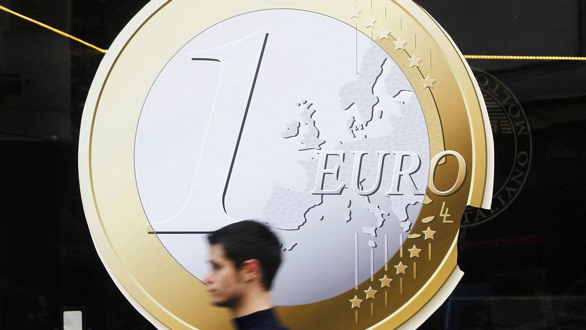 A man walks past a pizza shop using a sign of a euro coin to advertise its prices in central Madrid December 9, 2011.