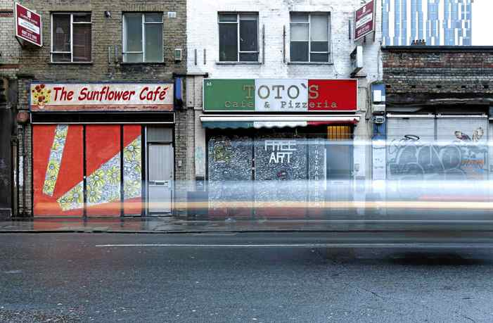 Traffic passes the painted shutters of closed shops in Shoreditch, in London